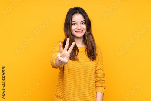 Fototapeta Young caucasian woman isolated on yellow background happy and counting three wit