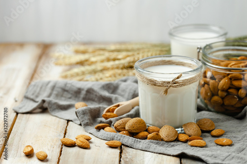 Fototapeta Fresh organic vegan almond milk. Alternative source of protein for vegetarians. Raw almonds as ingredients, peeled and unpeeled. Concept of healthy lifestyle. Closeup, wooden background obraz
