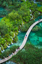 Tourists Walk By Wooden Path, In The Plitvice Lakes National Park  Which Is A UNESCO World Heritage Site.
