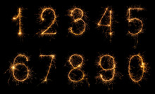 Set Of Burning Sparkler Numbers From 0 To 9 Made Of Bengal Fire, Sparkler Fireworks Candle Isolated On A Black Background. Party Dark Backdrop.