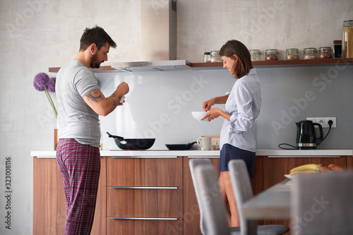 Fototapeta beautiful young couple making breakfast and coffee smiling in kitchen. young people, adults, modern, casual living concept obraz na płótnie