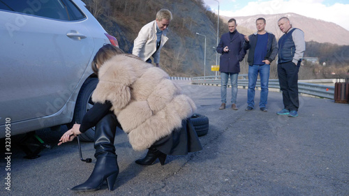 Fotografia two girls changing a car wheel on the side, and the men watching from the side