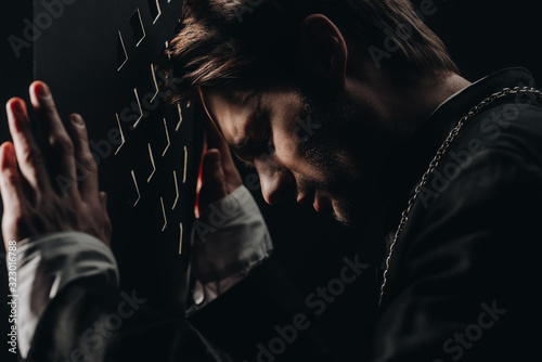 young tense catholic priest with closed eyes leaning on confessional grille in d Wallpaper Mural