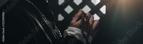 Photo partial view of catholic priest holding wooden rosary beads near confessional gr