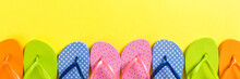 A Lot Of Flip Flop Colored Sandals, Summer Vacation On Colored Background, Banner Copy Space Top View