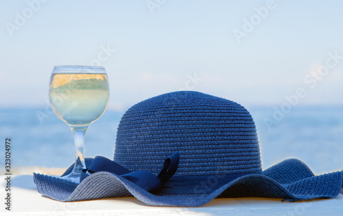 Valokuva A glass of white wine and a blue hat behind lagoon sea