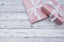 Two Pink Wrapped Presents Lying On White Wooden Surface, With Copy Space