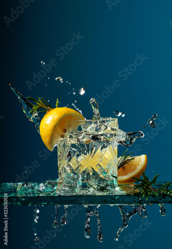 Fotografie, Obraz Cocktail gin-tonic with lemon and rosemary on a glass table.