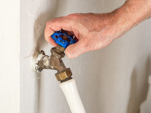 Man Turning On Outdoor Water Spigot For Watering Garden And Lawn Irrigation. Garden Hose Attached To A Classic Bronze Water Faucet With Blue Handle.