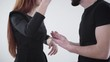 Unrecognizable Caucasian man and woman gesturing emotionally and yelling. Young married couple quarreling at white background indoors. Arguing, shouting, lifestyle.