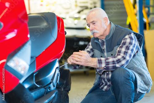 Photo portrait of senior mechanic fixing motocycle