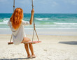 Beach summer vacation tropic palm style portrait of young beautiful girl on beach swing blue sea.Red haired woman swinging on the beach on Phu Quoc island, Vietnam. Happy on tropical palm tree swing.