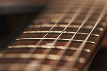 Macro Photo Of A Guitar Strings In Perspective. Parts Of The Guitar For Good Sound And Melody. Beautiful Musical Background In Red And Brown Tones.