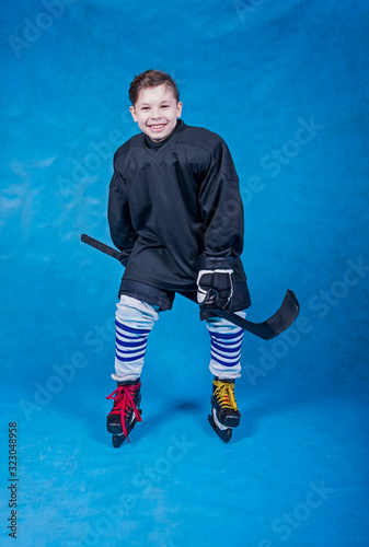 Young hockey player dancing without a helmet on a blue background Wallpaper Mural