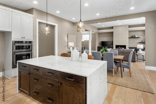 Fototapeta Kitchen and living room interior in new luxury home with open concept floor plan. Features island, hardwood floors, fireplace, dining area, and light filled spaces. obraz