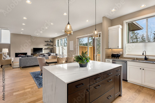 Kitchen and living room interior in new luxury home with open concept floor plan Fototapeta