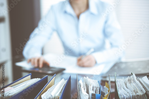 Photo Binders of papers waiting to process by bookkeeper woman or financial inspector, close-up