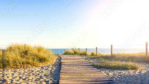 Photo Wooden path in the middle of the dunes leading to the beach surrounded by stakes