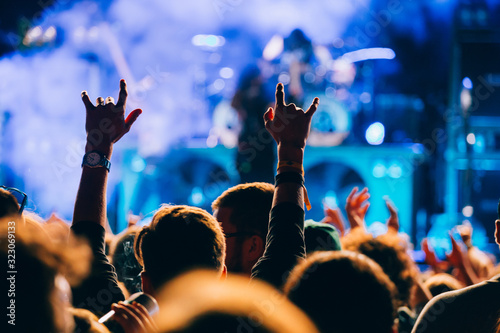 Concert and music festival background with hands raised and party people.