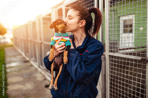 Young woman in dog shelter adopting a dog. Canvas Print