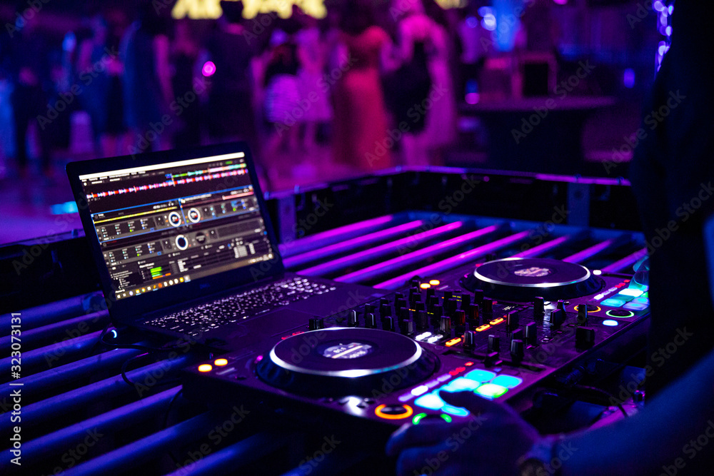 Fototapeta DJ plays live set and mixing music on turntable console at stage in the night club. Disc Jokey Hands on a sound mixer station at club party. DJ mixer controller panel for playing music and partying.