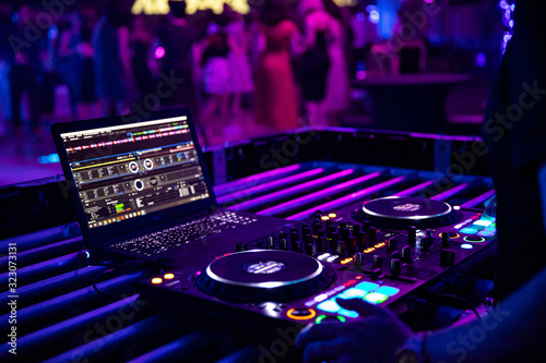 Fototapeta DJ plays live set and mixing music on turntable console at stage in the night club. Disc Jokey Hands on a sound mixer station at club party. DJ mixer controller panel for playing music and partying. obraz