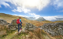 A Female Hiker And Their Dog Out Walking In The Mountains With Views Of Hayeswater And Summits Of Gray Crag, Thornthwaite And A Cloud Covered Stony Cove Pike In The Distance. Lake District UK.
