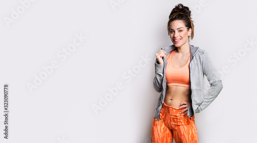 Fotografie, Obraz Studio photo of attractive positive young sporty woman with long hair in hood lo