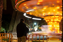 Man Waiting In A Carousel In Movement At Night