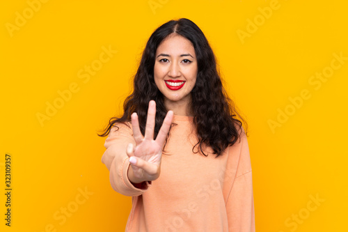 Spanish Chinese woman over isolated yellow background happy and counting three w Fototapete