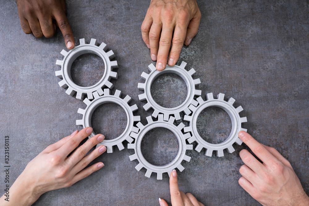 Fototapeta Businesspeople Joining Gears On Desk