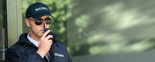 Young Security Guard Talking On Walkie-talkie Wallpaper Mural