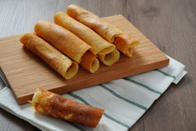 Filled Pancake Roll Assorted Flavors On Bamboo Chopping Board Placed On White And Green Striped Cloth On Wooden Table