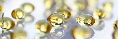 Foto Tablets scattered yellow fish oil on table of the pharmaceutical laboratory pill