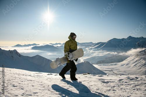Valokuvatapetti Guy with snowboard walks on sunny mountain top