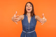 canvas print picture - Let me hug you! Friendly brunette woman in denim dress holding arms outstretched to embrace, welcoming with hospitable expression, caring person. indoor studio shot isolated on orange background
