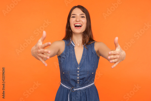 Let me hug you! Friendly brunette woman in denim dress holding arms outstretched to embrace, welcoming with hospitable expression, caring person Canvas Print