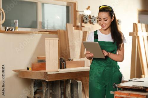 Obraz Professional carpenter in uniform with tablet near workbench - fototapety do salonu