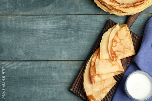 Fototapeta Flat lay composition with fresh thin pancakes on blue wooden table. Space for text obraz