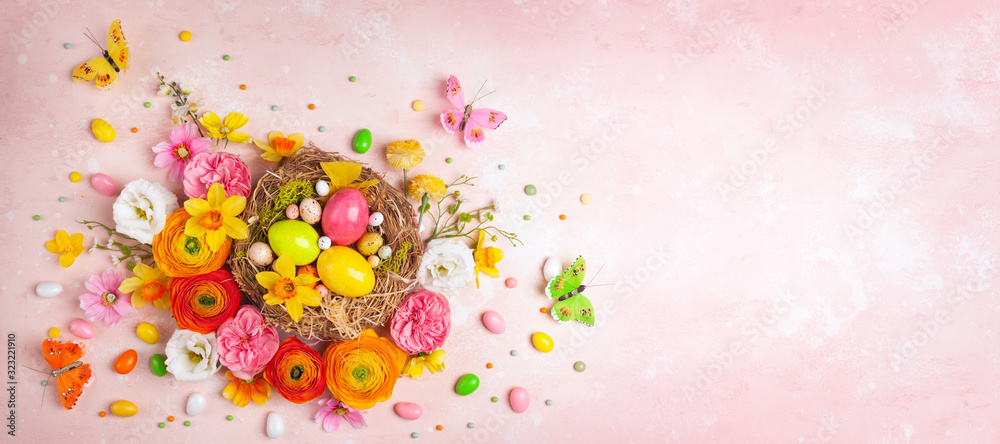 Fototapeta Creative holiday concept with easter eggs in nest, spring flowers and candy