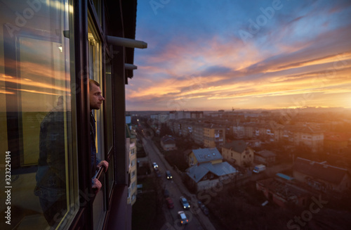 Fotomural Adult man stands on the balcony and looks into the distance enjoying the sunset