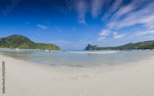 Soft focus Love Text on white sand beach with blue-green sea and mountain blurred in blue sky background, Loh Dalum Beach, Phi Phi Don island, Krabi, southern of Thailand Wallpaper Mural