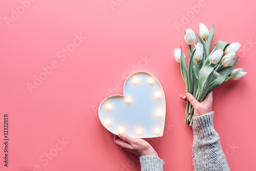 Obraz Springtime flat lay on pink, female woman hands holding bunch of white tulips, Spring flowers. Lightboard in heart shape in hands. Flat lay, top view, Mothers day or Valentine. - fototapety do salonu