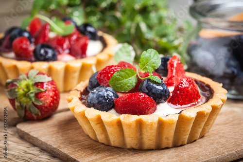 Fotografia Fresh homemade fruit tart with strawberries and blueberries.