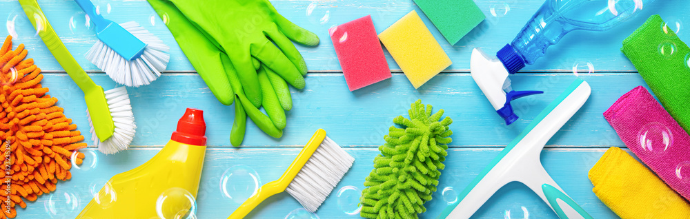 Fototapeta Colorfull cleaning items on blue wooden