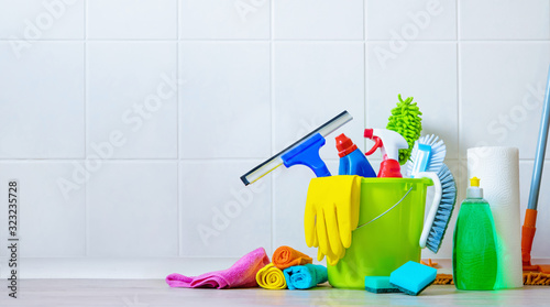 Fotomural Bucket of cleaning supplies in the front of tiled wall