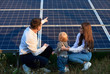Back view of young family of three crouching near photovoltaic solar panel, getting acquainted with alternative energy, modern family concept