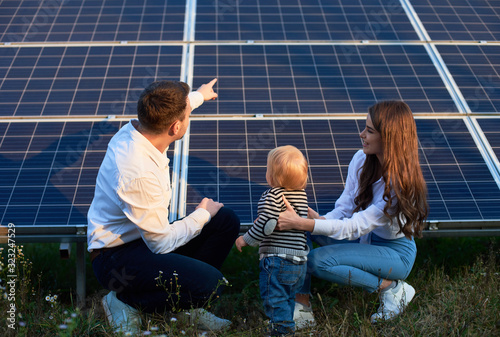 Photo Back view of young family of three crouching near photovoltaic solar panel, gett