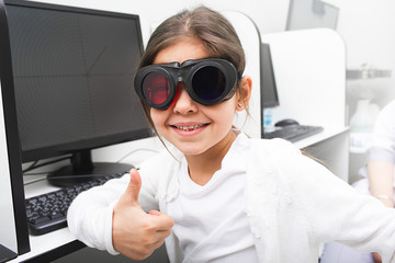 Little girl likes to receive computer treatment for her eyes. Strabismus treatment. Amblyopia treatment.