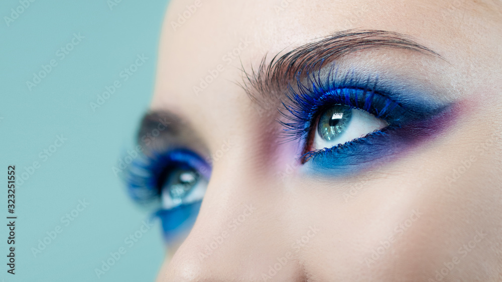 Fototapeta Glamorous bright eye makeup using the trend color classic blue, women's eyes close-up.